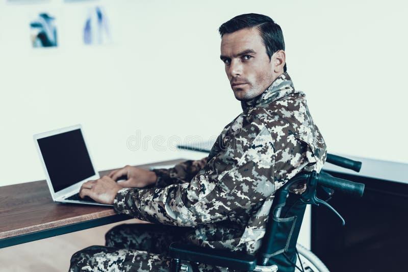 Allvarlig militär man i rullstolarbete på bärbara datorn royaltyfri bild