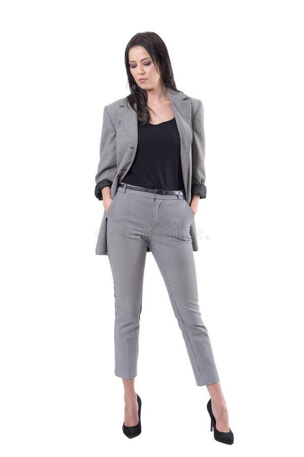 Allvarlig modekvinna i kläder för affärsdräkt som ner ser med händer i fack royaltyfri foto