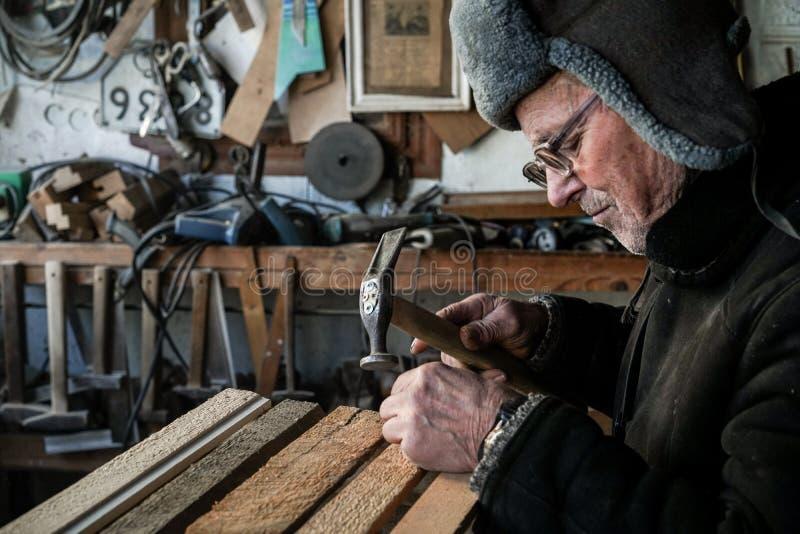 Allvarlig mogen gammal farfar i grå varm hatt, i glasögon royaltyfri fotografi