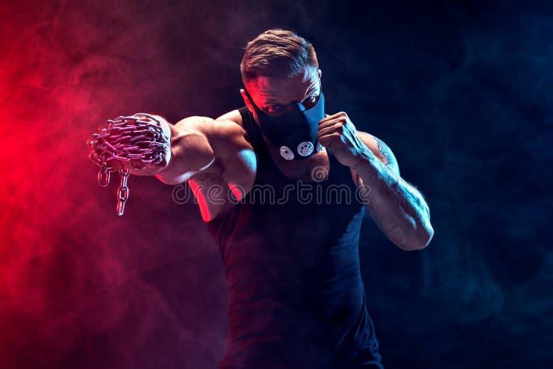 Allvarlig muskulös kämpe som gör stansmaskinen med kedjorna som flätas över hans näve royaltyfri bild