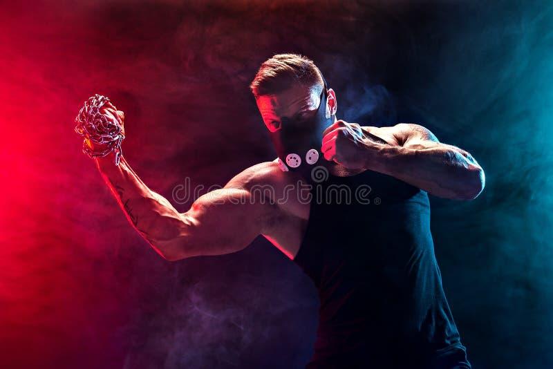 Allvarlig muskulös kämpe som gör stansmaskinen med kedjorna som flätas över hans näve arkivfoton