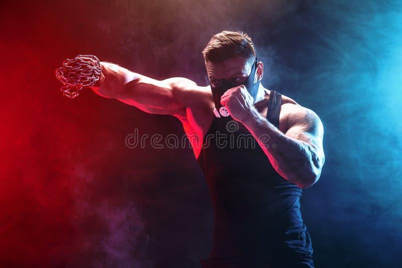 Allvarlig muskulös kämpe som gör stansmaskinen med kedjorna som flätas över hans näve royaltyfria bilder
