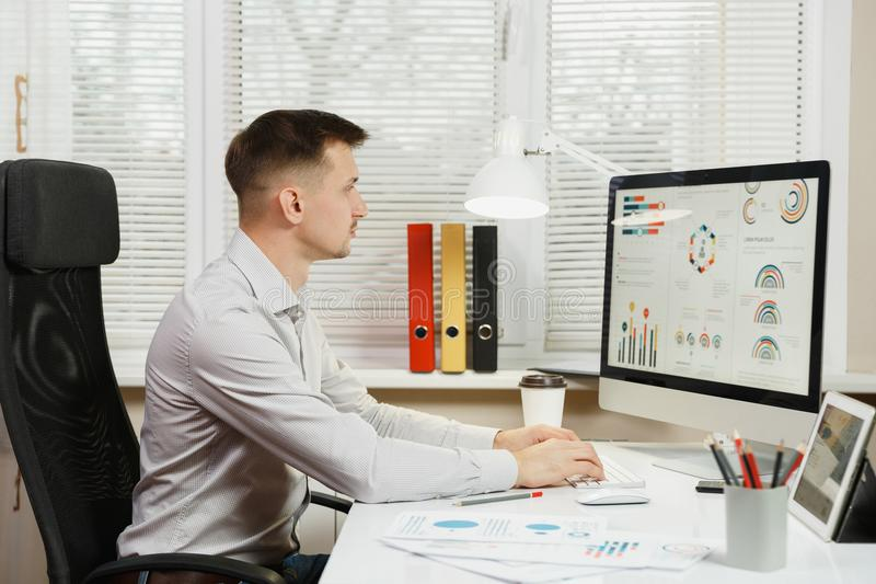 Allvarlig och fängslad affärsman i skjortasammanträde på skrivbordet som arbetar på datoren med den moderna bildskärmen Chef elle royaltyfri fotografi
