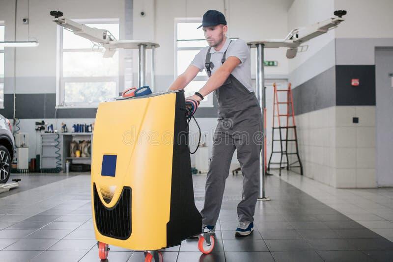 Allvarlig och koncentrerad ung man i enhetlig ställning på den rengörande maskinen och att luta på den Han ser på det gula medlet arkivbild