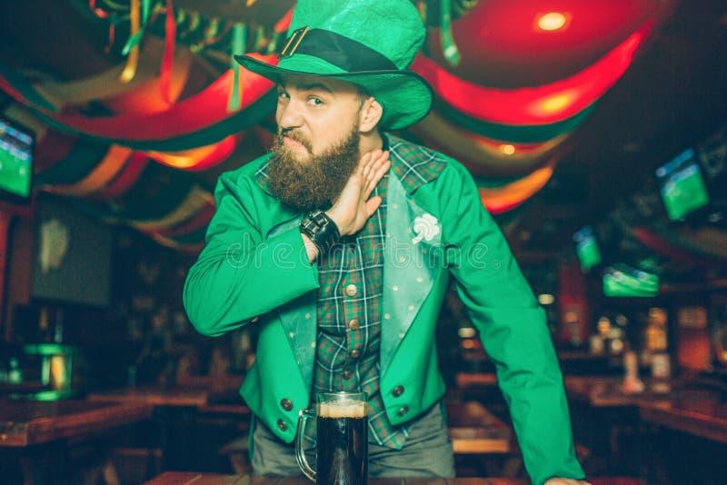 Allvarlig och tokig ung man i Sts Patrick dräktställning i bar och blick på kamera Han rymmer halsen för handen nästan Aggressivt arkivfoton