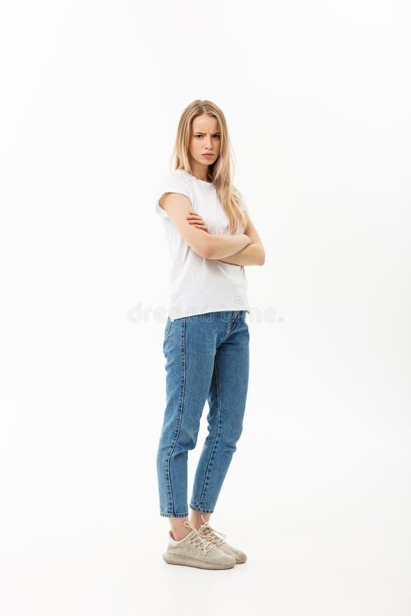 Allvarlig säker ung kvinna med det långa anseendet för tillfälliga kläder för blont hår som iklädda över ser kameran, full kropp royaltyfria foton