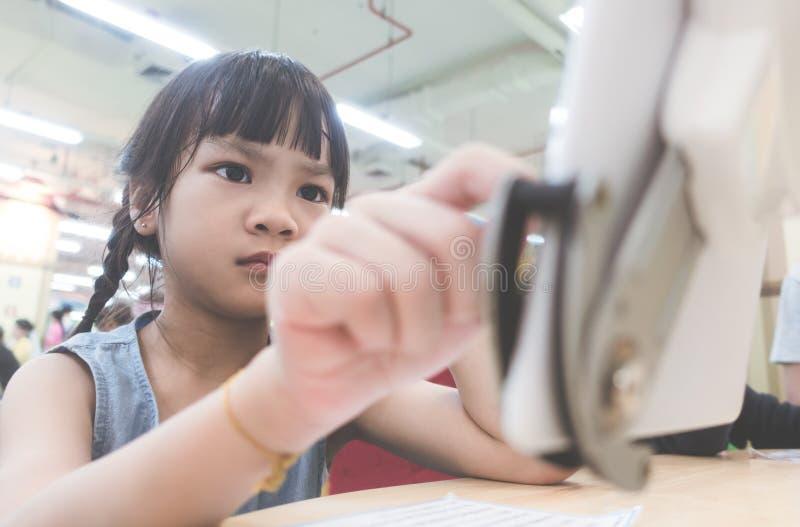 Allvarlig seende flickaunge som lär hur man använder den digitala minnestavlan arkivbild