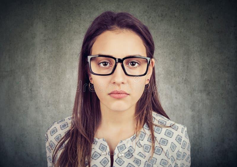 Allvarlig seende ung kvinna i exponeringsglas arkivfoto