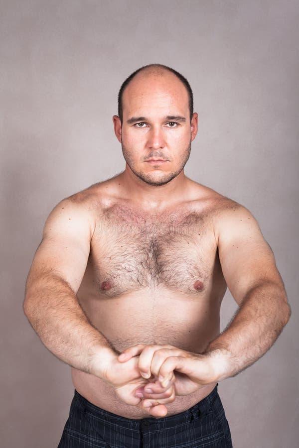 Allvarlig shirtless man som visar hans starka kropp fotografering för bildbyråer
