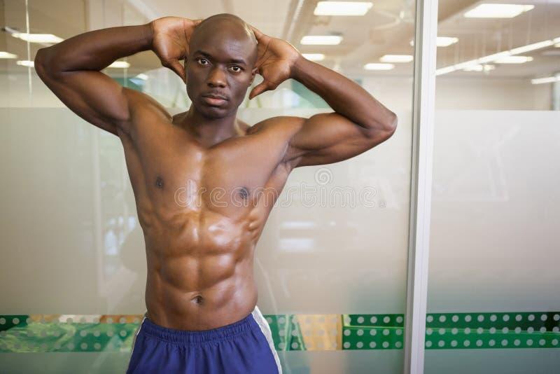Allvarlig shirtless muskulös man som poserar i idrottshall arkivfoto