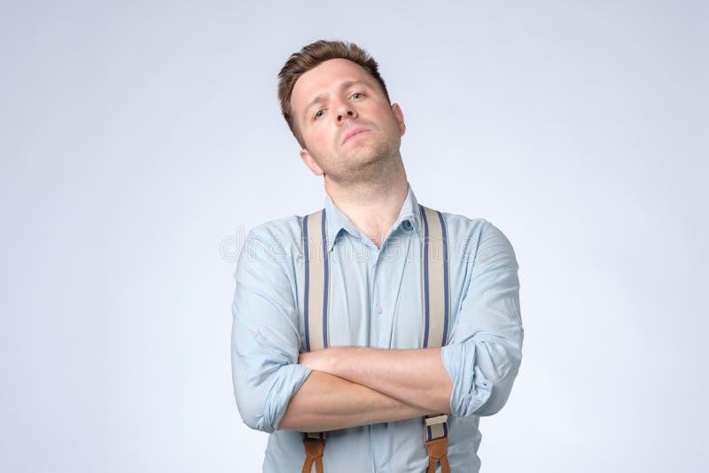 Allvarlig självisk man med vikta armar och hängslen som poserar på studion fotografering för bildbyråer