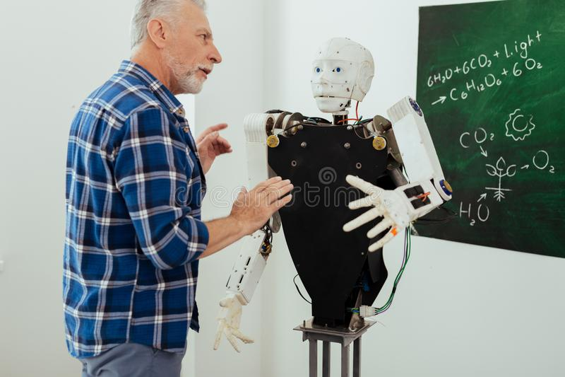 Allvarlig skäggig man som talar till roboten royaltyfri bild