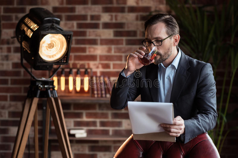 Allvarlig stilfull affärsman som tar en smutt av whisky arkivfoton