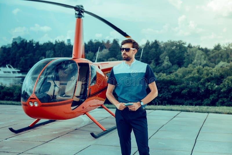 Allvarlig stilfull m?rkh?rig man i solglas?gon och v?ntande p? pilot f?r m?rk skjorta arkivfoton