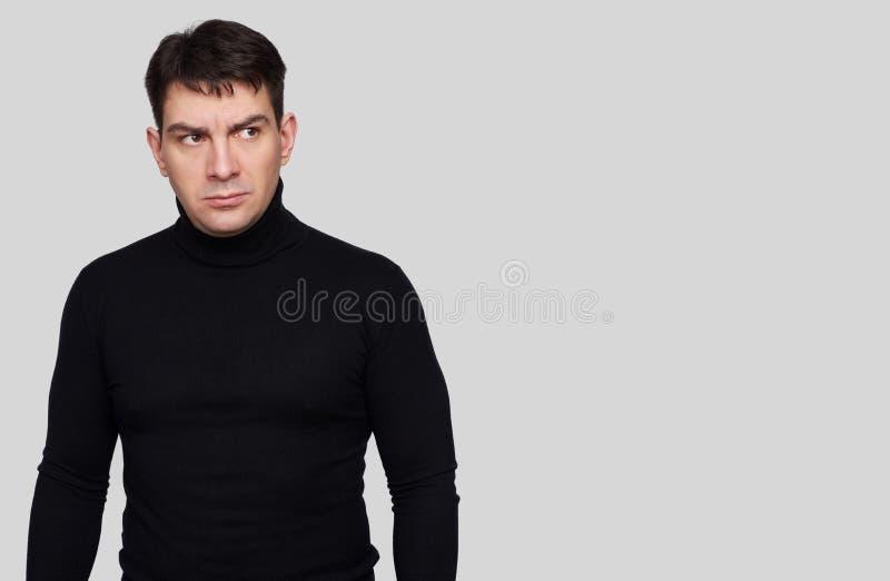 Allvarlig stilig man som bär den svarta halvpolokragen royaltyfri bild