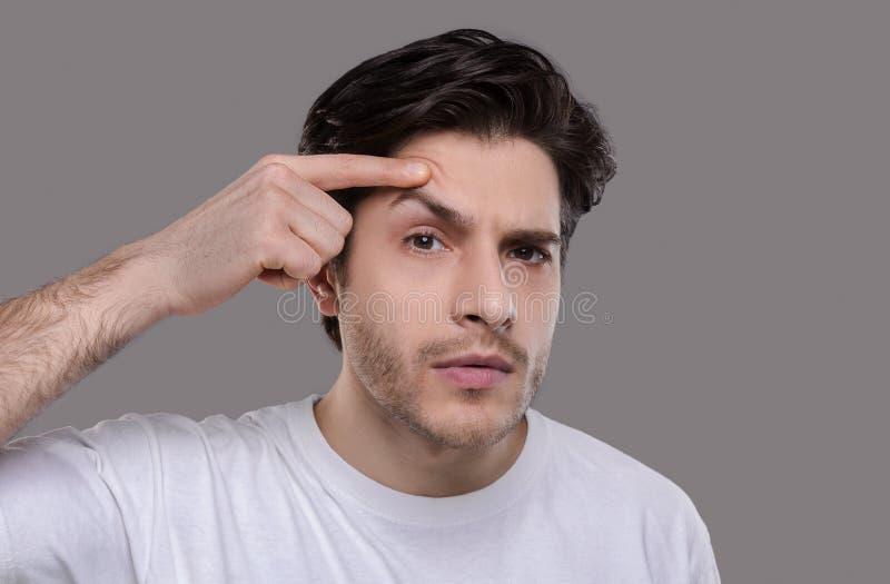 Allvarlig stilig man som ser hans framsida, undersökande skrynklor arkivfoton