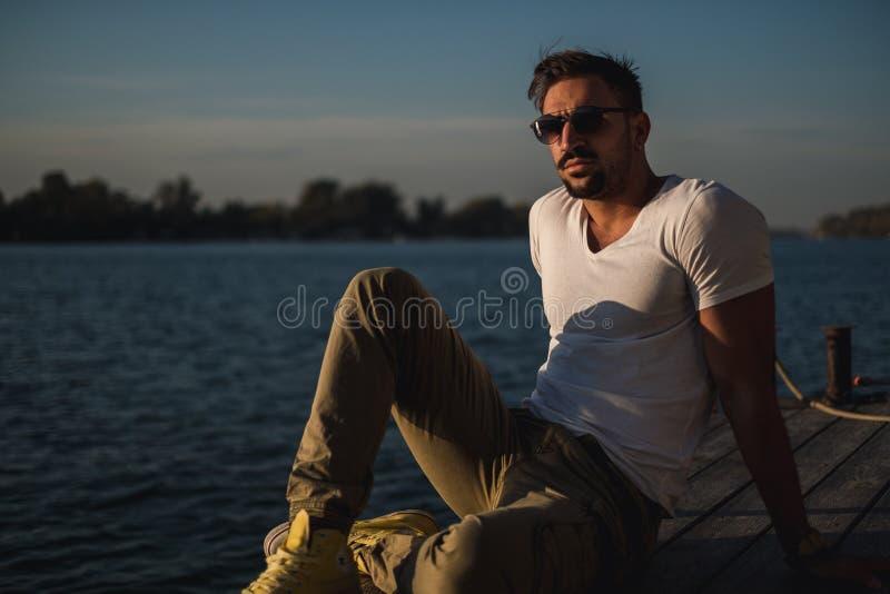 Allvarlig stilig man som tänker vid floden arkivfoto