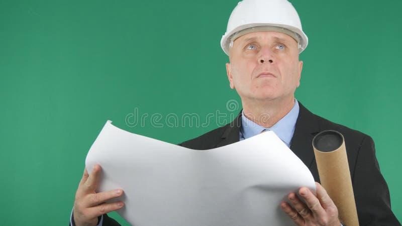 Allvarlig tekniker Reading ett konstruktionsplan med den gröna skärmen i bakgrund royaltyfria foton