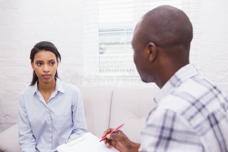 Allvarlig terapeut som lyssnar till hans talande patient royaltyfri foto