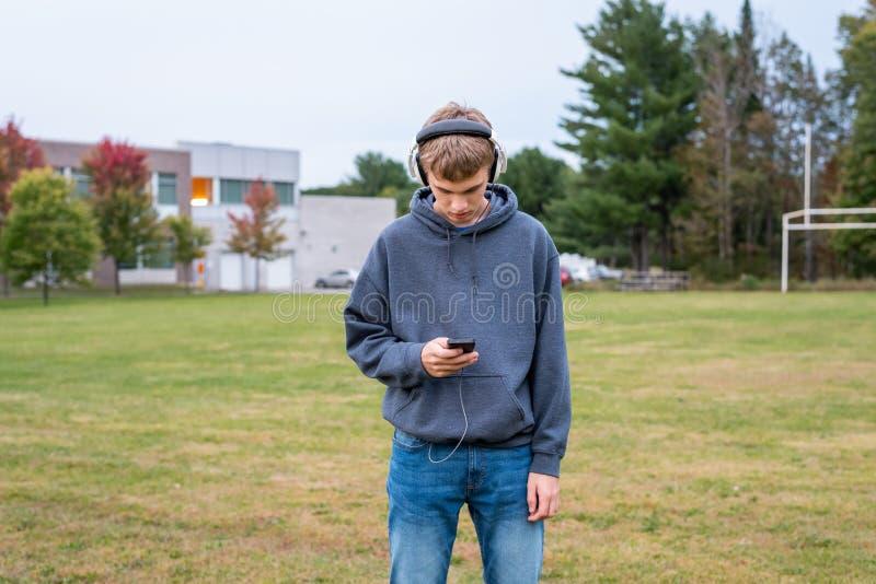 Allvarlig tonåring som lyssnar till musik royaltyfri foto