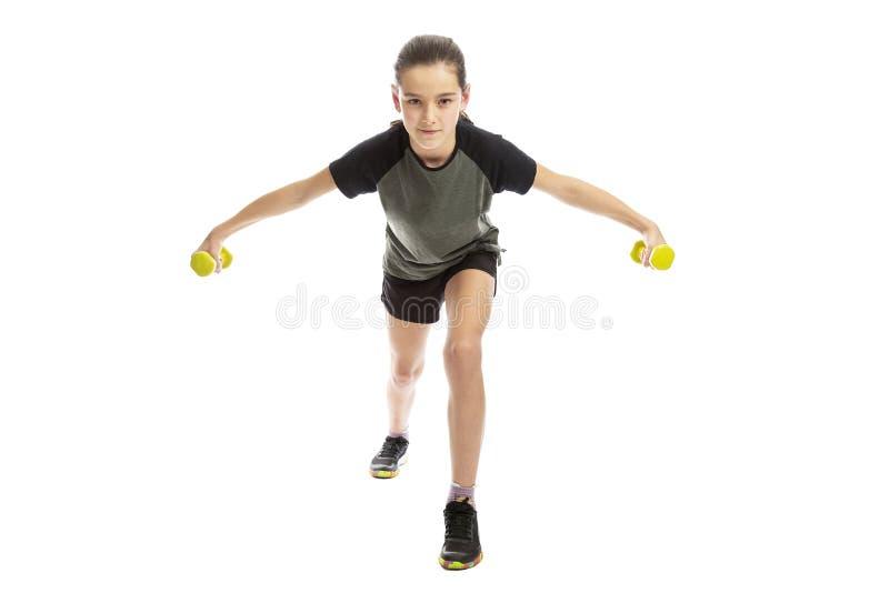 Allvarlig tonåringflicka i sportswearen som gör övning med hantlar bakgrund isolerad white royaltyfri foto