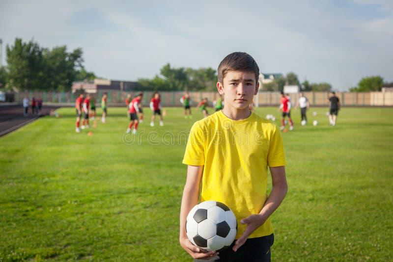 Allvarlig tonårs- pojke med en fotbollboll i hans hand mot bet royaltyfria foton