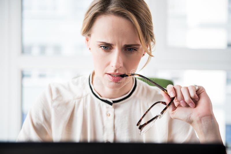 Allvarlig trött kvinnlig chef som håller eyewearen royaltyfri foto