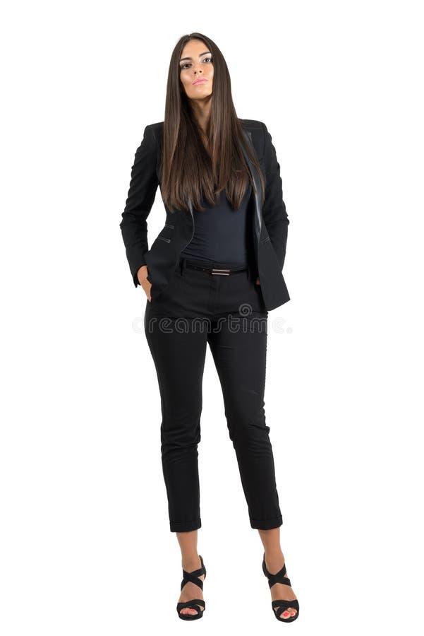 Allvarlig ung affärskvinna med händer i fack som ser kameran arkivfoton