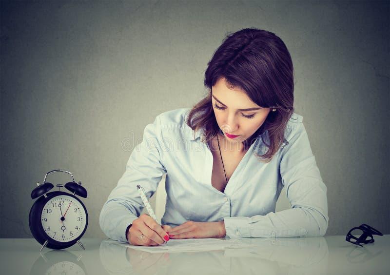 Allvarlig ung affärskvinna som ut skrivar ett brev, eller fyllnads- en ansökningsblankett royaltyfri bild