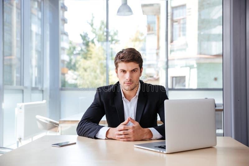 Allvarlig ung affärsman med bärbara datorn som i regeringsställning sitter arkivbilder