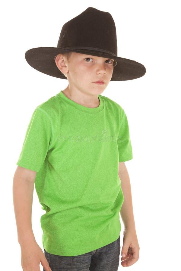 Allvarlig ung hatt för cowboy för pojkegräsplanskjorta arkivfoto