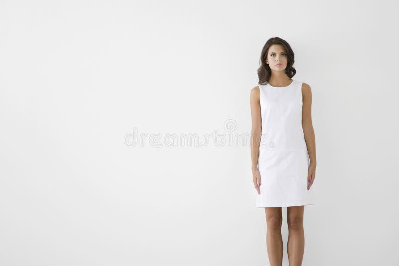 Allvarlig ung kvinna i den vita klänningen royaltyfria bilder
