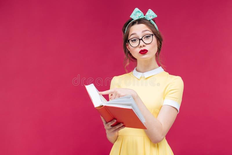 Allvarlig ung kvinna i exponeringsglas som står och läser en bok royaltyfri foto