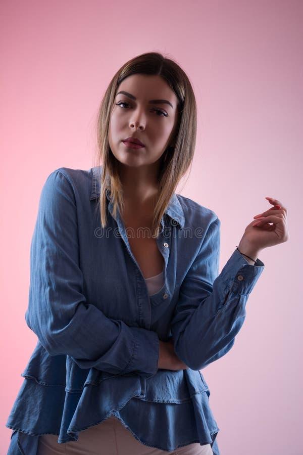 Allvarlig ung kvinna med handen och fingrar i luft i den blåa skjortan som ser kameran i studion som isoleras på rosa färger royaltyfria bilder