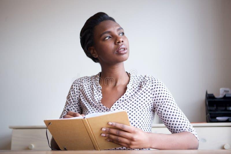 Allvarlig ung kvinna som tänker och skriver i tidskrift royaltyfri bild