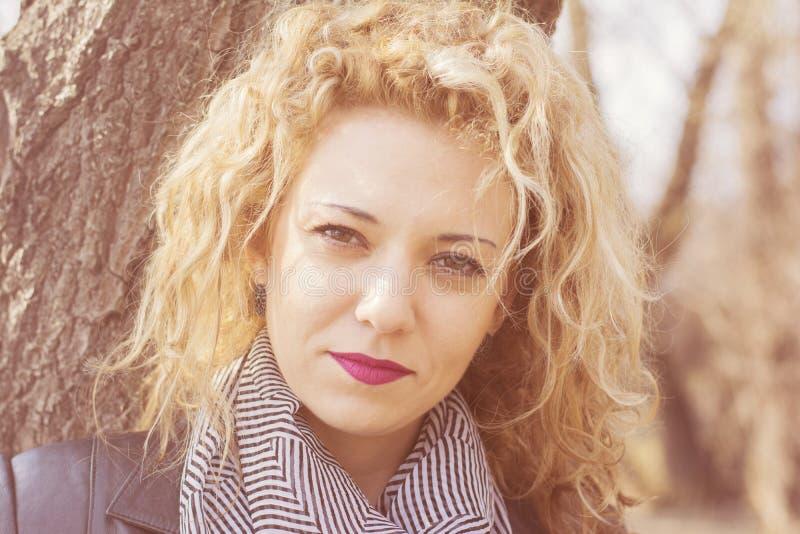 Allvarlig ung lockig blond kvinna royaltyfri fotografi