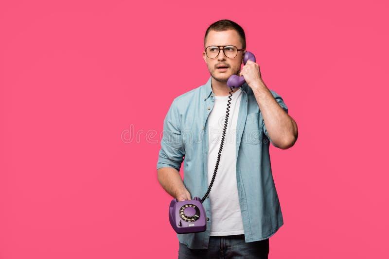 allvarlig ung man i glasögon som talar vid den isolerade tappningtelefonen royaltyfri fotografi