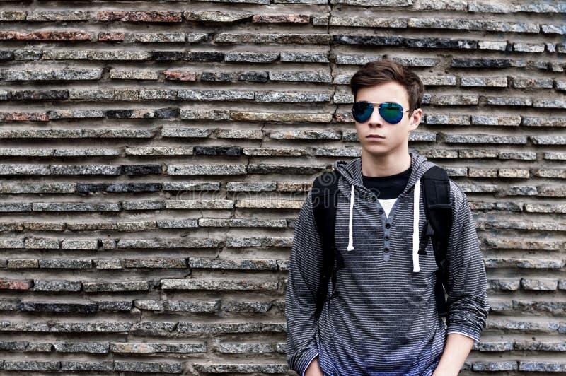 Allvarlig ung man nära väggen av stenar royaltyfria foton