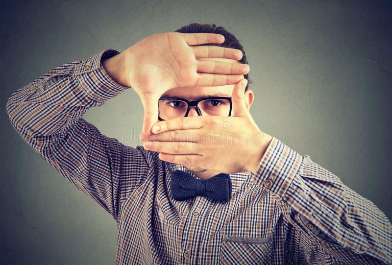 Allvarlig ung man som gör en ram med hans händer som ser kameran royaltyfria bilder