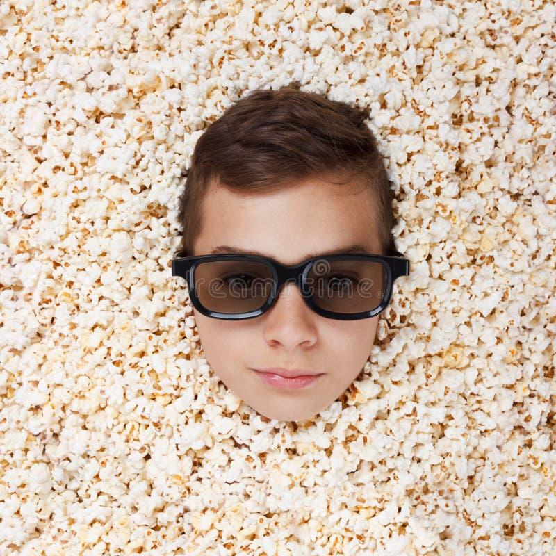 Allvarlig ung pojke i stereo- exponeringsglas som ser ut ur popcorn arkivfoton