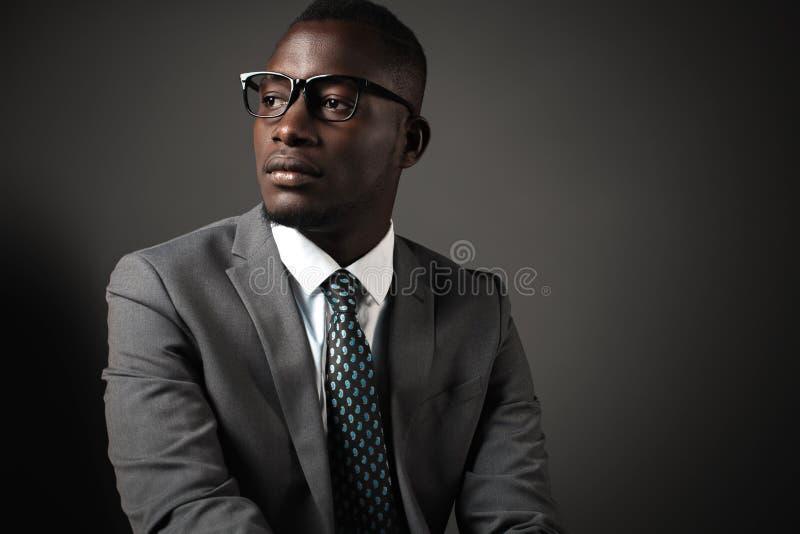 Allvarlig ung svart man med exponeringsglas och den gråa affärsdräkten royaltyfria bilder