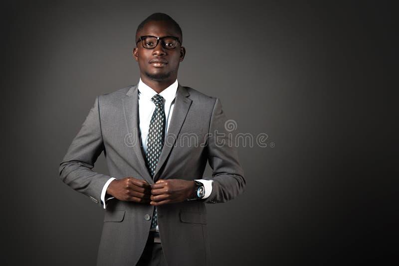 Allvarlig ung svart man med exponeringsglas och den gråa affärsdräkten royaltyfri bild