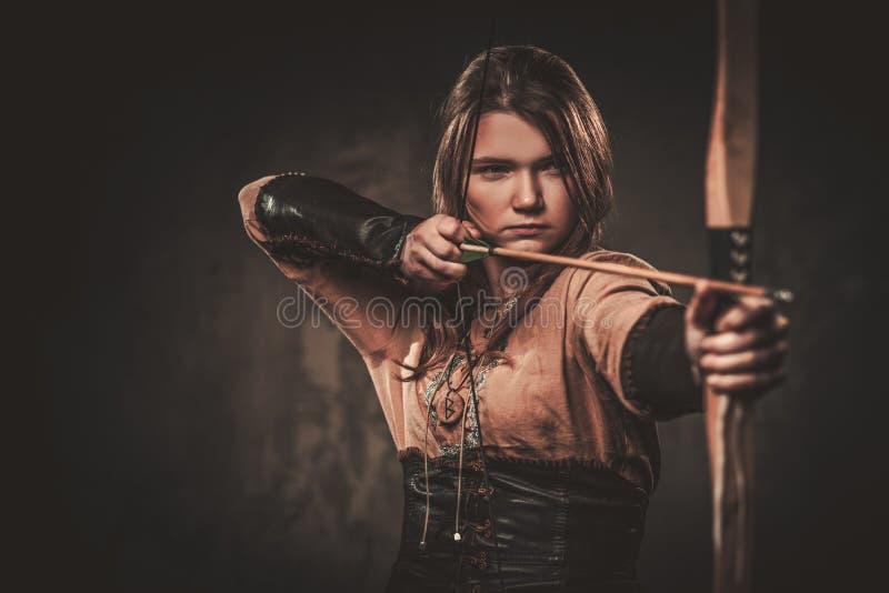 Allvarlig viking kvinna med pilbågen och pilen i traditionell kläder för en krigare som poserar på en mörk bakgrund royaltyfria foton