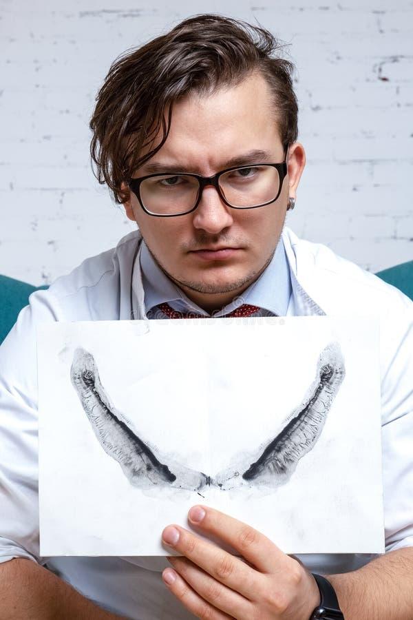 Allvarlig yrkesmässig psykolog som visar papper med den Rorschach inkbloten royaltyfri fotografi
