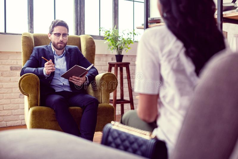 Allvarlig yrkesmässig terapeut som frågar frågor till hans patient arkivfoton
