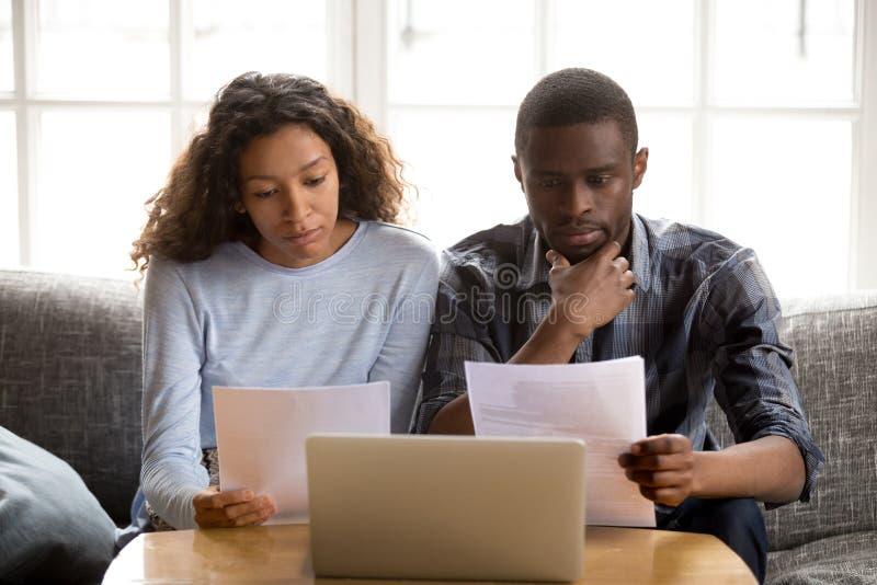 Allvarliga afrikansk amerikanpar som läser pappers- dokument royaltyfri bild