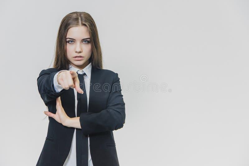 Allvarliga nätta brunhåriga kvinnapunkter till kameran med hennes finger, på den vita bakgrunden close upp kopia royaltyfria foton