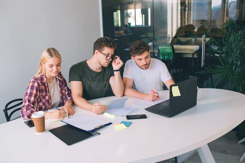 Allvarliga och koncentrerade ungdomararbetar tillsammans i ett rum De sitter på tabellen Den unga kvinnan skriver i anteckningsbo arkivfoton