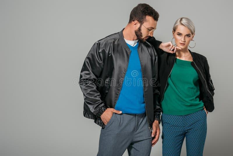 allvarliga par av modeller i stilfulla dräkter royaltyfri fotografi
