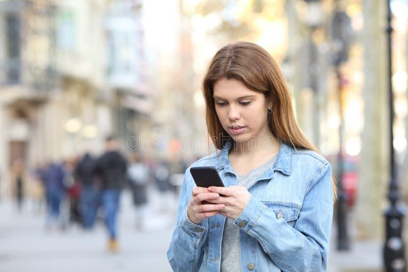 Allvarliga smsande meddelanden för tonårs- flicka på telefonen arkivfoto